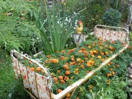 Fun garden decorations and recycling ideas for yard landscaping Colorful  flower bed in spiral shape Recycling old bed for unusual flower bed