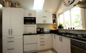 This timeless black and white country style kitchen has thermal wrapped  patterned doors with a black granite benchtop This design makes the most  of the