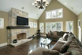 brown living room walls vaulted ceiling and sculpted metal chandelier hang above a wide expanse of