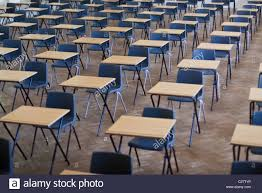 desks and chairs set out for exams in a school hall uk