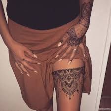 подвязка в виде великолепных узоров тату на бедре у девушки