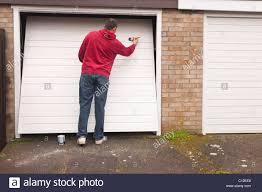 Decorating garage man door images : A MODEL RELEASED man doing DIY painting a garage door in the Uk ...