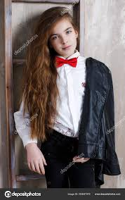 a beautiful teenage girl with long chestnut colored hair and blue eyes dressed in a white shirt with a red bow tie and black jeans holds a black leather