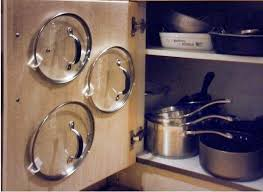 TIP: Keep saucepan lids organised and easy to find by strategically placing  adhesive hooks behind
