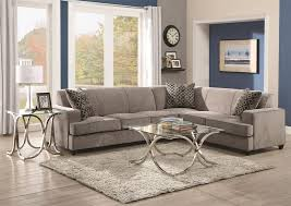 cozy overstuffed sectional with inviting cushions wooden floor white rug square coffee table gray sofa with motif cushions blue painted wall pictures white