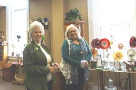 black forest broadcasting carol jackson l and deb plummer r share a light moment during sunday s open house at the potter county artisan center next to some glass art by becky