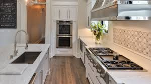light color marble countertops kitchen island with sink cutout and countertop with cooktop stove