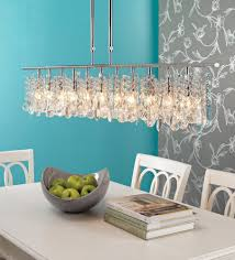 hanging low modern crystal linear chandelier above solid wooden dining table painted with white color decor ideas