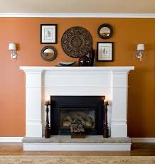 white wooden fireplace with two wooden candlesticks against a terra cotta wall