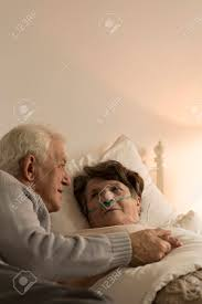 Sickly Light Elderly Man Taking Care Of His Sickly Wife Who Is Lying In Bed