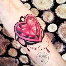 бриллиант в виде сердца с подвеской тату на предплечье у девушки