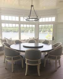 transitional dining room chandelier kitchen nook kitchen nook with custom round table and chairs with a window seat under bay windows with transoms and