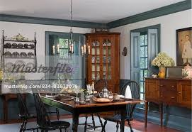 dining room colonial style wall shelf with pewter collection corner cupboard windsor style chairs witha plank top table spring flowers dado