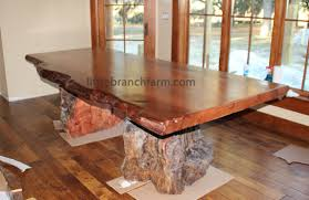 the large rustic table also features western cedar root bases wood slab tables
