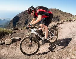 cyclist riding a white muddyfox mountain bike down a steep hill with helmet and backpack