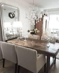 vanha puinen pöytä kauniisti kimalteleva kristallivalaisin ja korkea peili luovat monipuolisen kattauksen tilan tunnelmaan