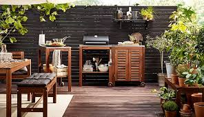 several pieces of outdoor furniture in dark brown acacia hardwood including tables chairs benches