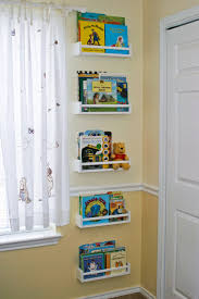 small white tiered wall shelves for books aside patterned window curtains