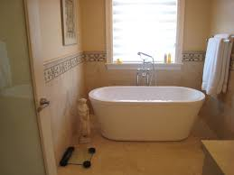 interior oval white small freestanding bathtub on beige tile floor connected by beige wall