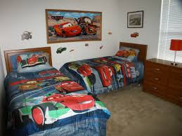 minimaist car themed wooden twin bed with cars comforters also added brown wood varnish cabinets red