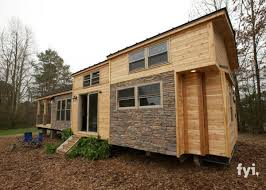 Here is our knock out of a tiny house. The exterior embodies a rustic charm  with its combination of light wood and stone-colored bricks.