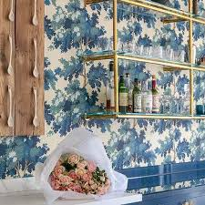 glass and brass wall mount shelving unit over blue cabinets