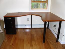 wooden top l shaped ikea desk with file cabinet on one base and four legs