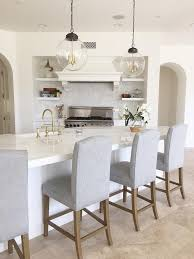 kitchen features calcutta marble countertops with antique newport brass chesterfield faucet and restoration hardware hudson camelback fabric stools