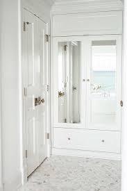calcutta gold marble hexagon tiles dress the floors of a closet near glossy white bifold bathroom closet doors