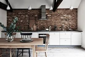white cabinets with gray countertop dark brown brick backsplash wooden dining table with black chair 4 pendant lights slide in gas range and hood cutting
