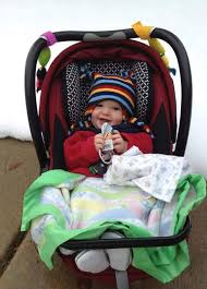 this baby is safely strapped in to his seat with a coat on backward on the top and a blanket on his lap to keep him nice and warm photo by heather lentz
