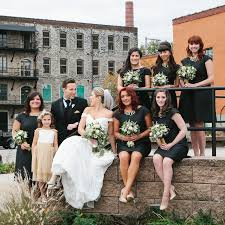 modern bride with bridesmaids in black and gold in front of moulin at sherman mills in