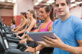 gym instructor male gym instructor with women on treadmills in gym stock photo