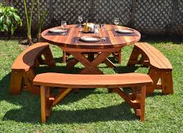 small round outdoor wooden picnic table with separate benches on green grass garden ideas