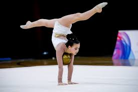floor gymnastics moves. Rhythmic Gymnast Performs Handstand In Splits Balancing Her Ball Floor Gymnastics Moves