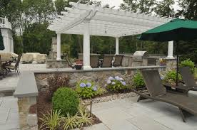 outdoor kitchen with natural stone veneer and pergola