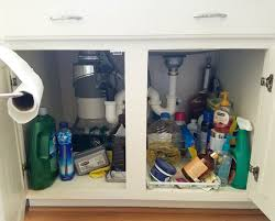 A Messy Cabinet Under The Kitchen Sink With Cleaning Products In Disarray.