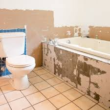 bathroom with tile removed from tub and walls