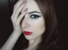 with smoky eye makeup double eyeliner and red glossy lips is showing her makeup