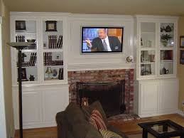 white entertainment center with tv over fireplace