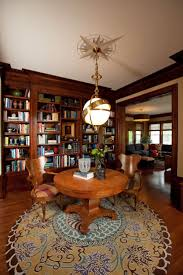 brilliant home office library ideas with wooden library cupboard and antique hanging lamp over round oak wood pedestal library table equipped double brown brilliant home office design ideas
