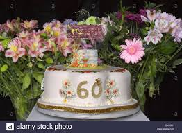 A 60th Birthday Cake With Wishing Well On Top And Cut Flowers In The