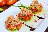 avocado tower with tomato and almond sauce  and some shrimp