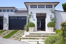 white brick home with black garage doors