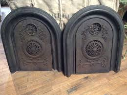 pr of antique arched cast iron fireplace covers