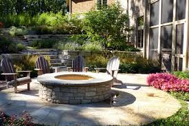 raised stone fire pit on flagstone patio