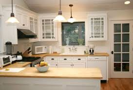 kitchen white wooden kitchen cabinet and brown wooden countertops connected by three pendant lamps