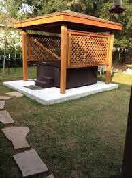 a hot tub positioned on a cement pad in a backyard with a protective wooden  gazebo