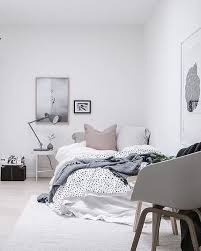Oversized pillows and a cool color palette in a casual Swedish bedroom.