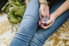 a woman sitting holding a small purple crystal in her hands